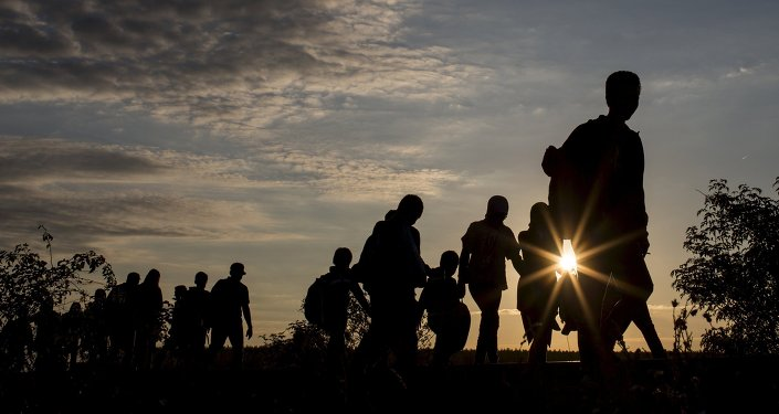 Migrants walk along rail tracks as they arrive at a collection point in the village of Roszke, Hungary, September 8, 2015