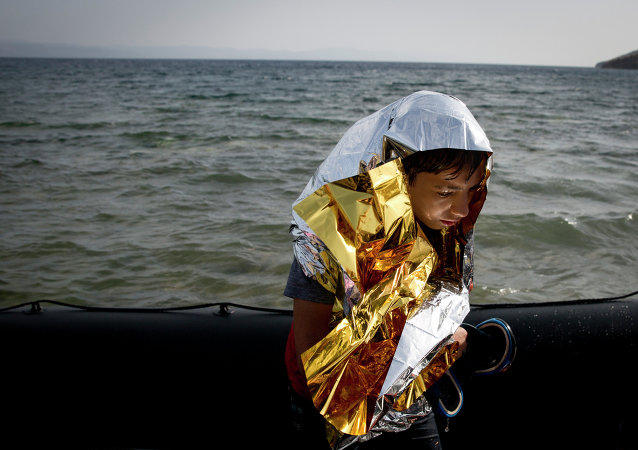 A young Syrian boy is wrapped with a thermal blanket as he arrives with others at the coast on a dinghy after crossing from Turkey, at the island of Lesbos, Greece, Monday, Sept. 7, 2015.