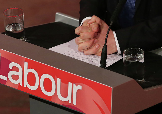 Britain's Labour party leader Ed Miliband holds his hands on his notes as he delivers a speech on international development at the Almeida Theatre, London, Sunday, April 26, 2015. Britain goes to the polls in a general election on May 7.