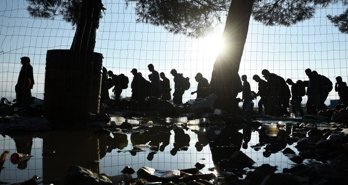 The sun rises as refugees and migrants walk to pass from the northern Greek village of Idomeni to southern Macedonia, Friday, September 11, 2015. The sudden onset of autumn has taken tens of thousands by surprise all along the Balkans route from Greece to Hungary