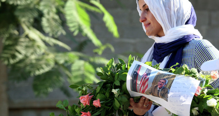 Libyan woman carries a wreath with a photo of US Ambassador Chris Stevens on it as she and others gather to pay their respect to the victims of the Tuesday, Sept. 11, 2012 attack on the US consulate, in Benghazi, Libya, Monday, Sept. 17, 2012.