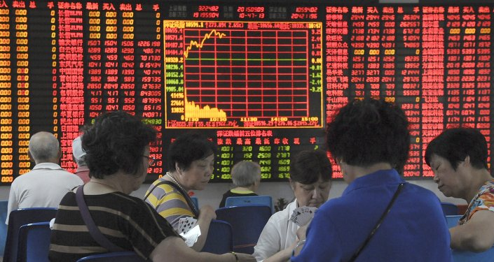 Investors play cards in front of an electronic board showing stock information at a brokerage house in Shanghai, China, September 9, 2015.
