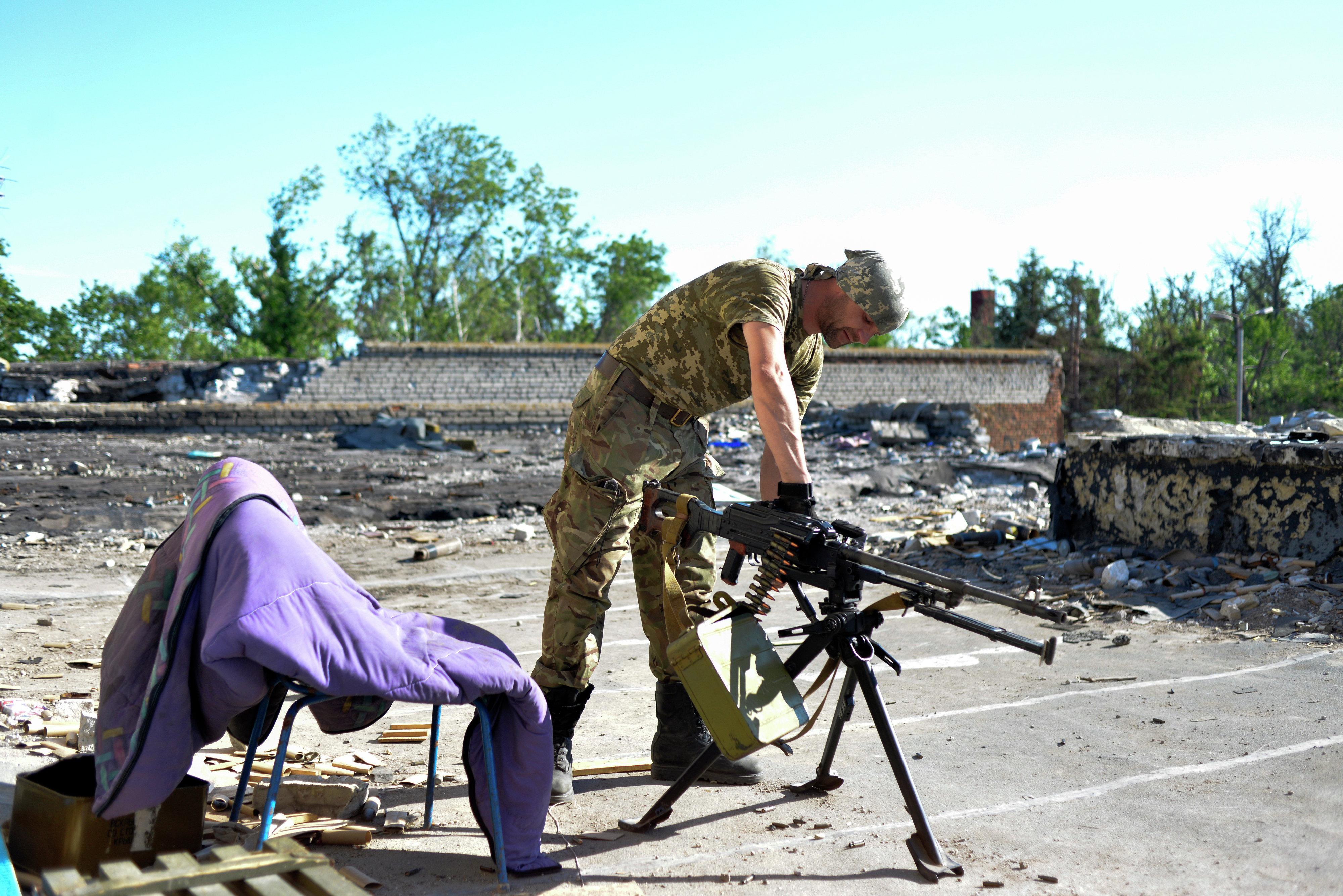 Serviceman of Ukrainian volunteers battalion of Donbass prepares a machine gun on the positions near the village of Shirokine, Donetsk region on June 6, 2015