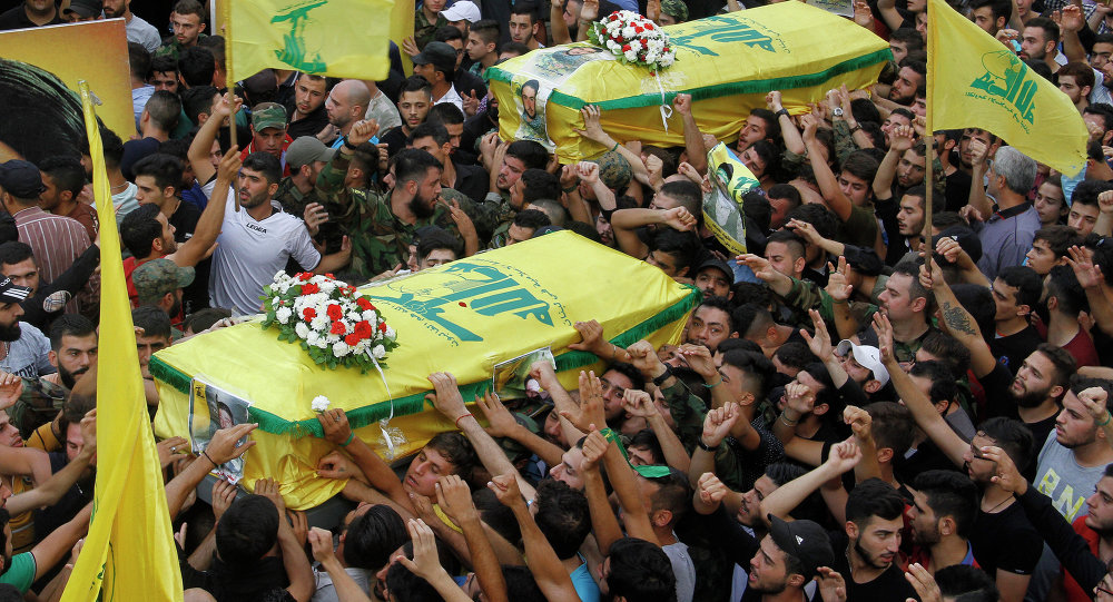 Mourners carry the coffins of two members of Lebanon's Shiite Hezbollah movement who were killed in combat alongside Syrian government forces fighting against Islamic State group jihadists in Syria's Qalamun region boarding Lebanon, during their funeral procession in a southern suburb of Beirut, on September 11, 2015