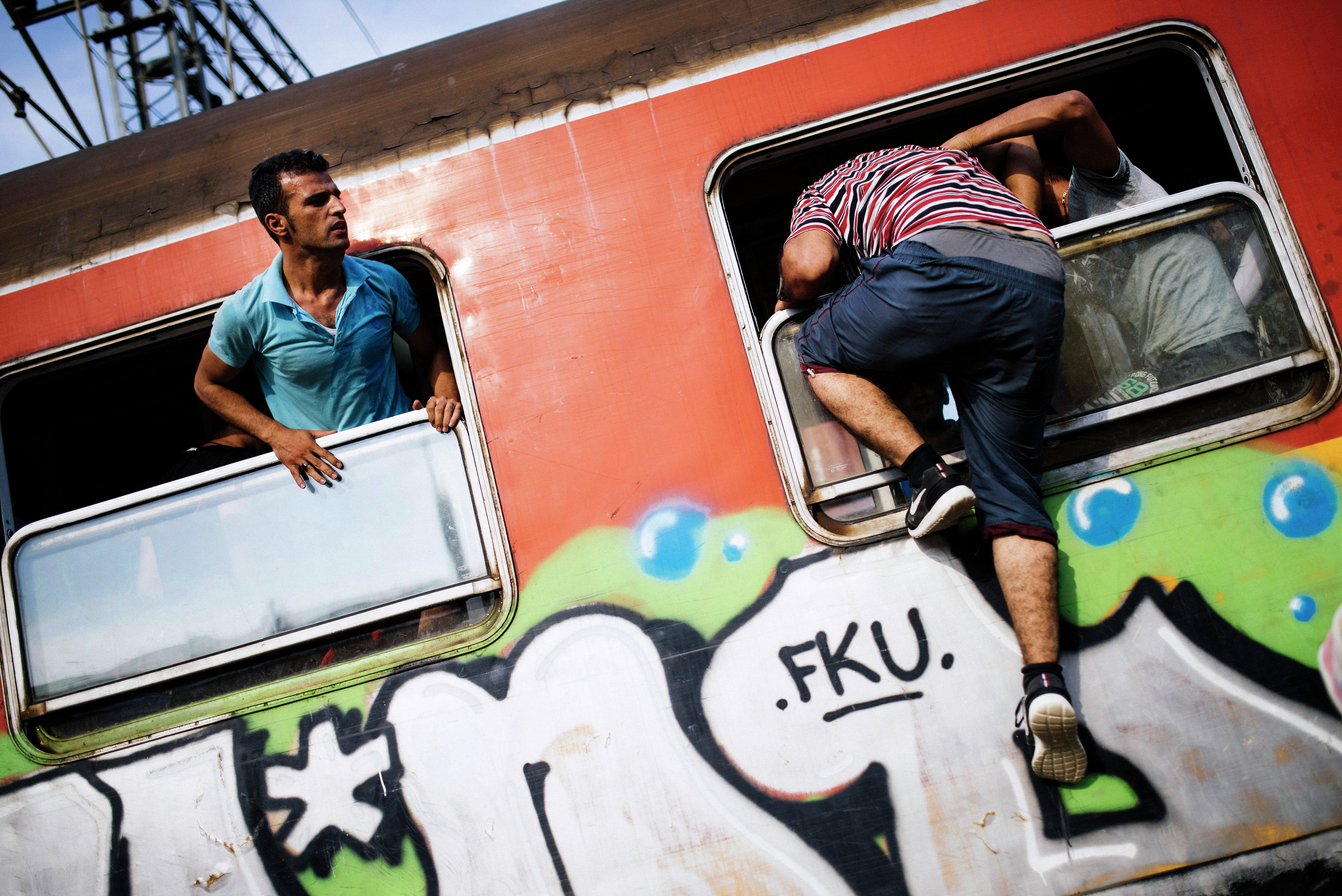 A migrant climbs through a window onto a train heading to the border with Serbia at the train station of Gevgelija, on the Macedonian-Greek border, on August 6, 2015
