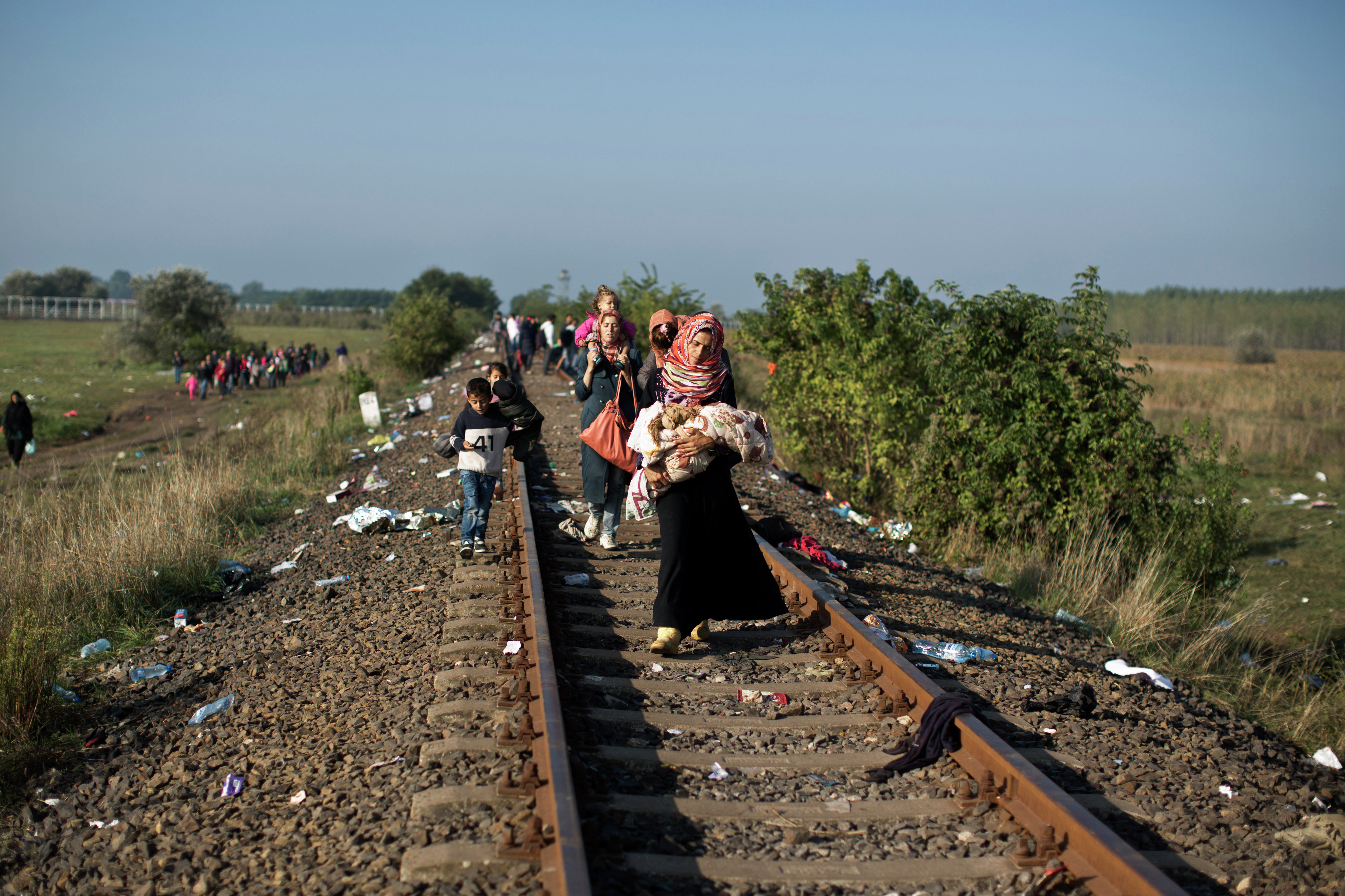 Syrian women carrying their children make their way along a railway track after crossing the Serbian-Hungarian border near Roszke, southern Hungary, Sunday, Sept. 13, 2015