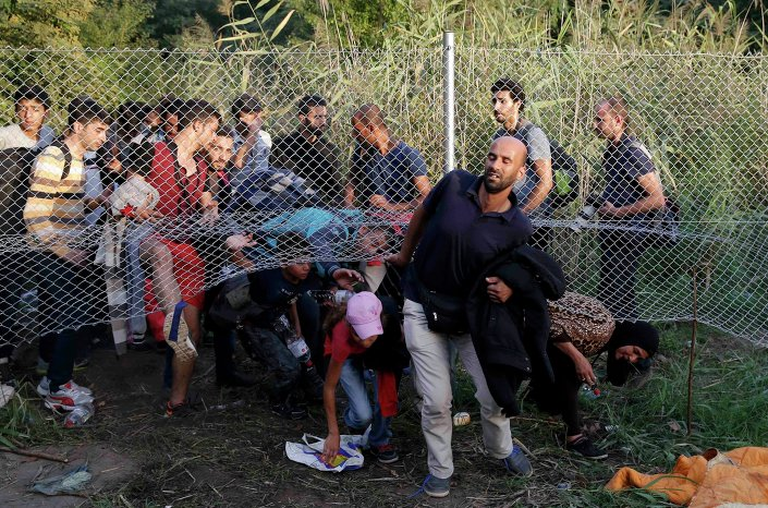 Migrants pass under a highway security fence as they try to find a new way to enter Hungary after Hungarian police sealed the border with Serbia near the village of Horgos, Serbia, September 14, 2015