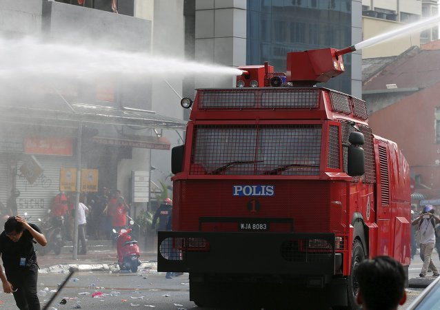 A Red Shirt demonstrator runs away from a water cannon used during a rally to celebrate Malaysia Day and to counter a massive protest held over two days last month that called for Prime Minister Najib Razak's resignation over a graft scandal, in Malaysia's capital city of Kuala Lumpur September 16, 2015.
