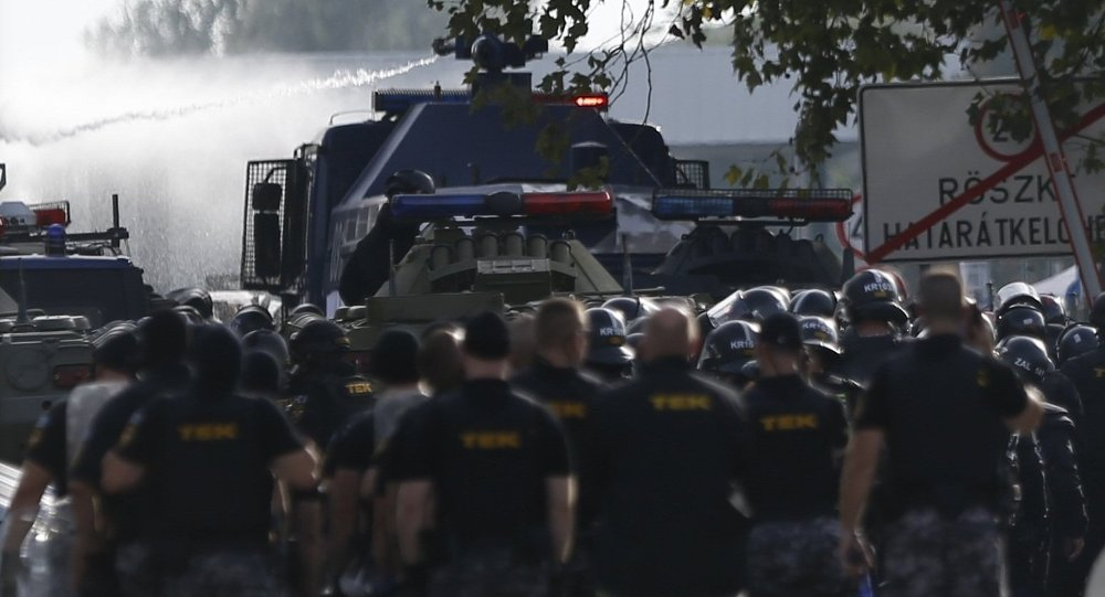Hungarian riot policemen fire a water cannon as migrants protest on the Serbian side of the border crossing in Roszke, Hungary September 16, 2015