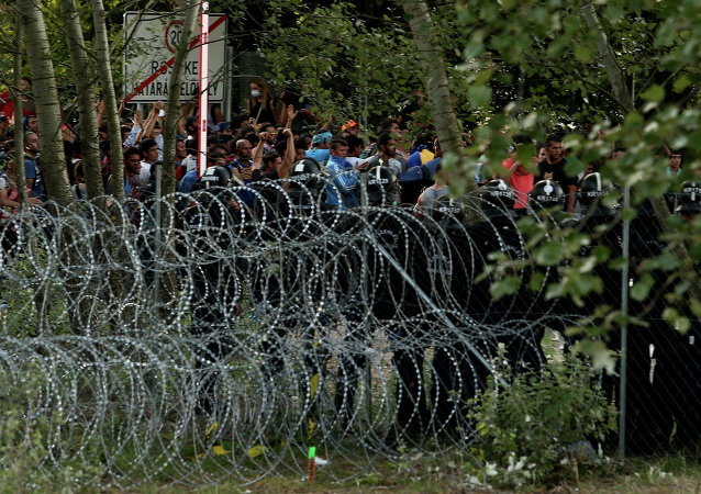 Hungarian riot police secure the border as migrants attempt to break out from the no-man's land between the two countries at the Hungarian-Serbian border of Roszke station