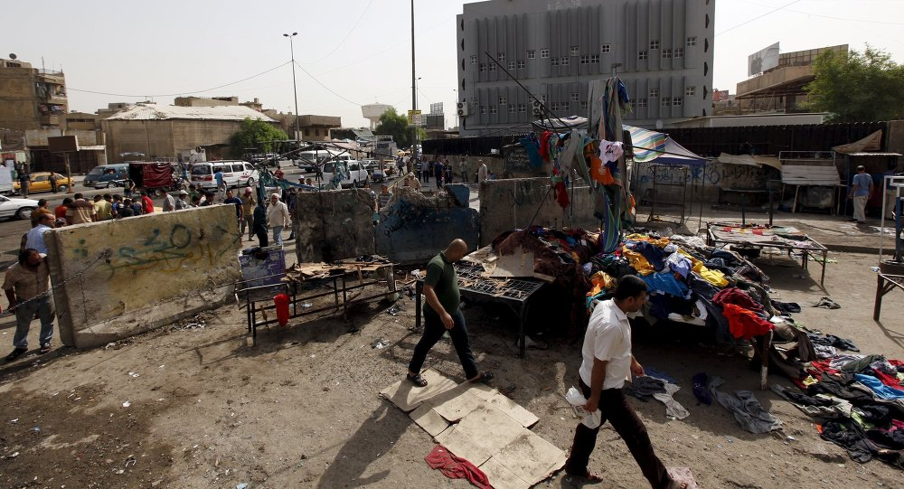 Men walk past the site of a suicide bomb attack in Baghdad, Iraq