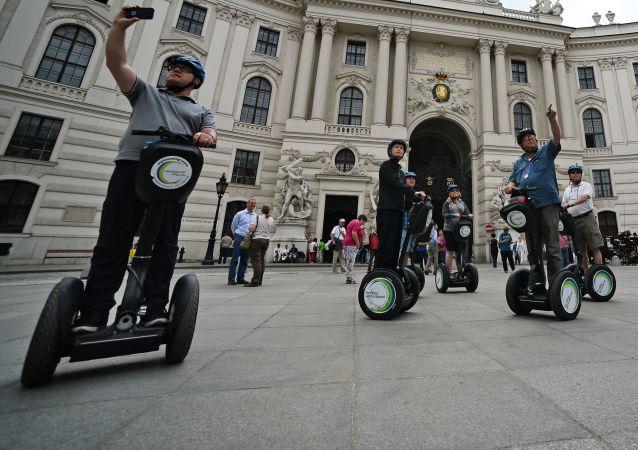 Туристы катаются на сигвее у императорской резиденции Хофбург в Вене, Австрия