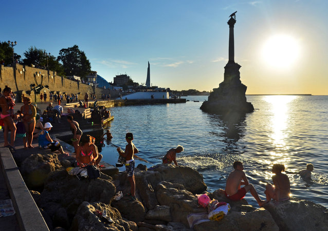 Holidaymakers and local residents bathe at dusk near a monument to sunken ships  in Sevastopol