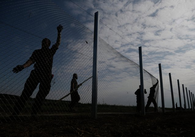 Hungarian soldiers work on a fence that is being built at the border with Croatia, near the village of Beremend, Hungary, Tuesday, September 22, 2015.