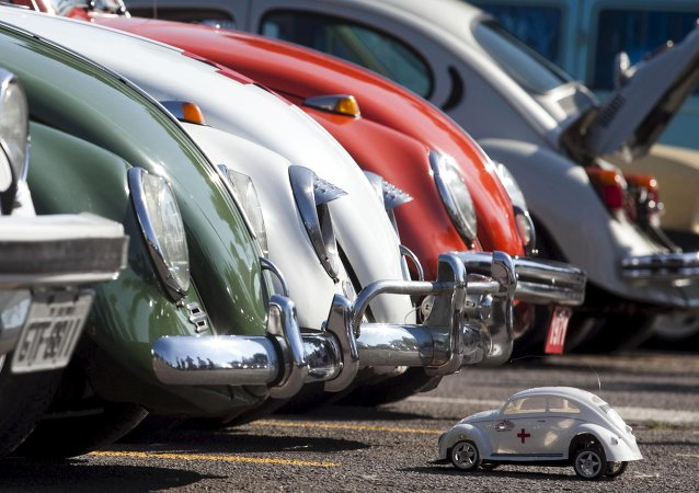 A Volkswagen Beetle toy is seen in front of Beetle cars