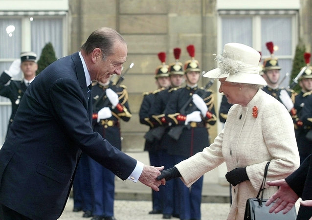 Queen Elizabeth II and French President Jacques Chirac shake hands as Republican Guards salute the queen's arrival at the Elysee Palace in Paris Monday, April 5, 2004, as she started a three-day state visit to France to mark 100 years of formal friendship between France and Britain.