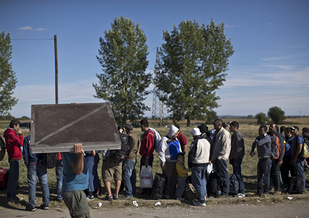 People queue in order to get inside a newly established reception center for migrants and refugees close to Croatia's border with Serbia, in the town of Opatovac, Croatia