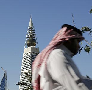 A Saudi man passes the al-Faisaliya tower in Riyadh, Saudi Arabia