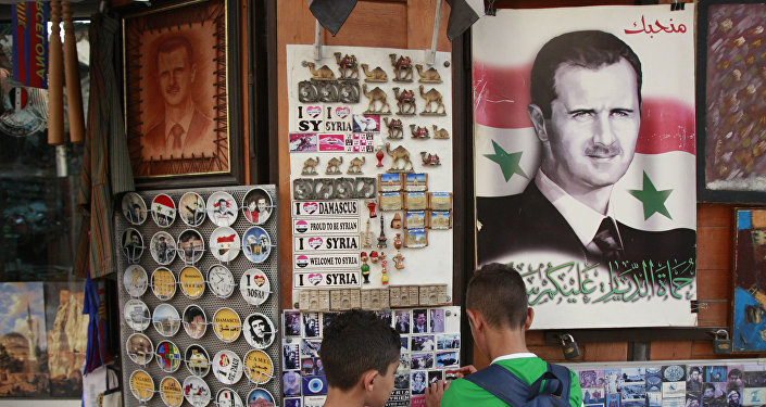 Syrian students, look for souvenir items at a shop displaying a portrait of Syrian President Bashar Assad with Arabic legend reads We love you, in the old city of Damascus, Syria