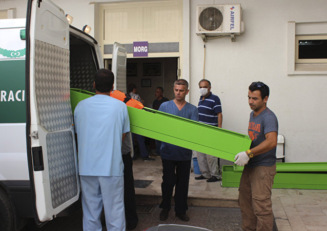 People upload coffins with the bodies of migrants that were drowned while they were trying to cross on a boat to the nearby Greek island of Kos, to the hospital's morgue at the coastal town of Bodrum, Turkey, Sunday, Sept. 27, 2015. Turkey's coast guard says that 17 migrants have drowned after a vessel carrying them toward Greece sank in the Aegean Sea