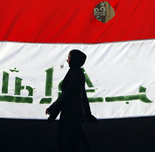 An Iraqi woman walks her national flag during a celebration marking the the departure of US troops from Iraq in Baghdad's Adhamiyah neighbourhood. File photo