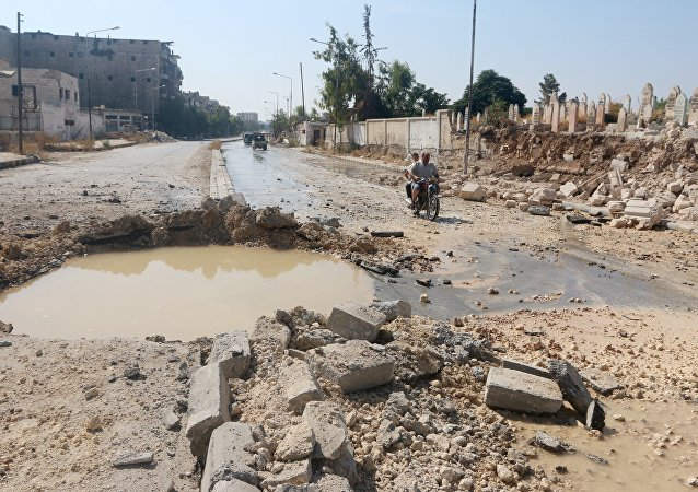 Residents ride a motorbike past a crater filled with water in Aleppo's al-Shaar neighborhood, Syria September 28, 2015.