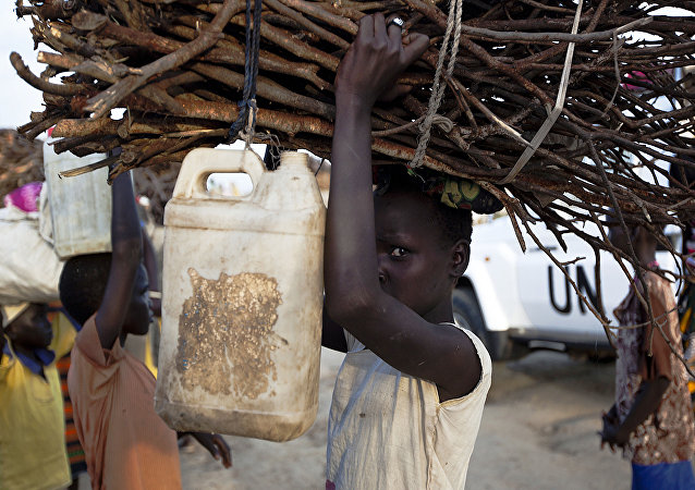 A young woman carries firewood after returning to the United Nations base outside Bentiu, at the end of the day, on September 20, 2015