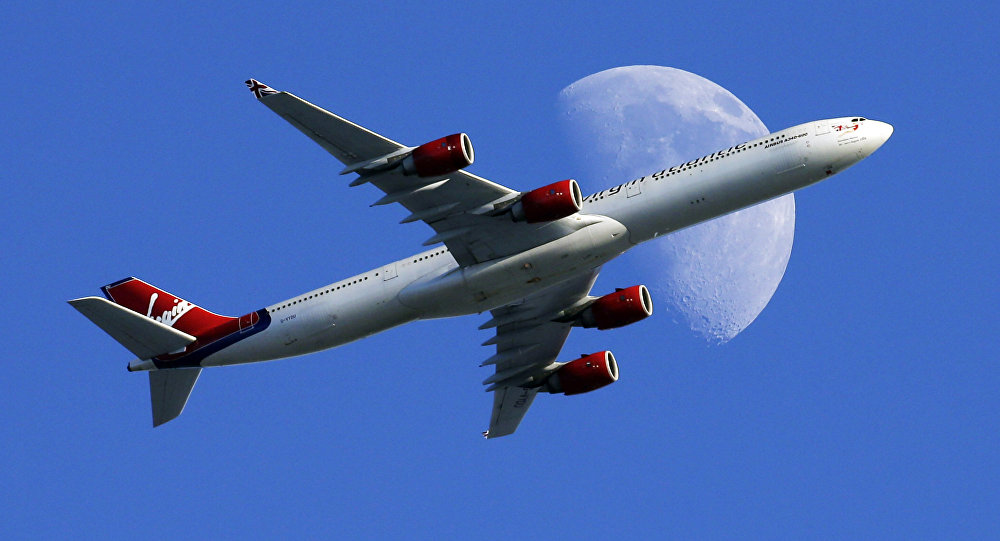 A Virgin Atlantic passenger plane crosses a waxing gibbous moon on its way to the Los Angeles International Airport, Sunday, Aug. 23, 2015, in Whittier, Calif