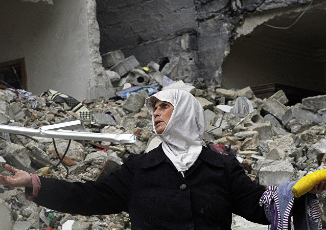 Syrian woman stands amid the ruins of her house . Syria (File)