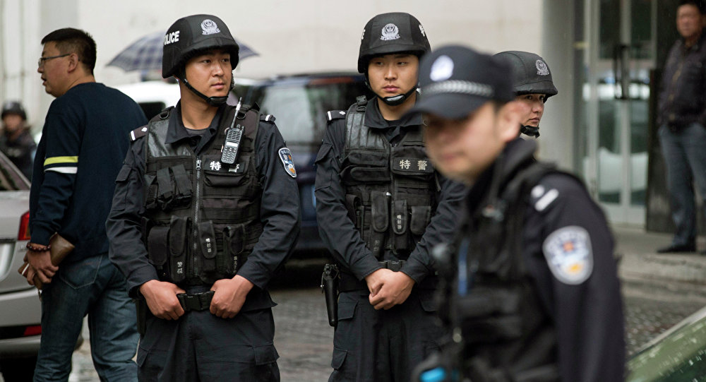 Armed policemen stand guard near the site of an explosion in Urumqi, northwest China's Xinjiang region, Thursday, May 22, 2014