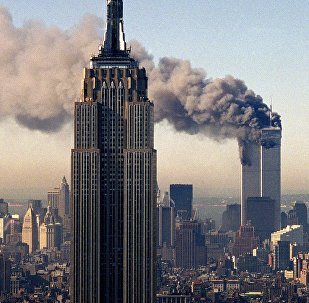 In this file photo, the twin towers of the World Trade Center burn behind the Empire State Building in New York.