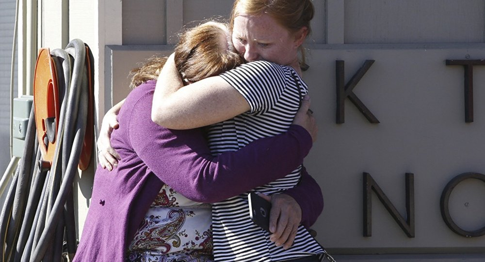Umpqua Community College alumnus Donice Smith (L) is embraced after she said one of her former teachers was shot dead, near the site of a mass shooting at Umpqua Community College in Roseburg,Oregon October 1, 2015