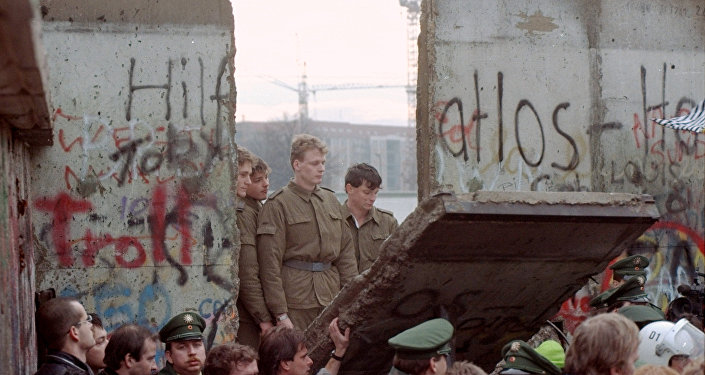 East German border guards look through a hole in the Berlin wall after demonstrators pulled down one segment of the wall at Brandenburg gate in this November 11, 1989 file picture