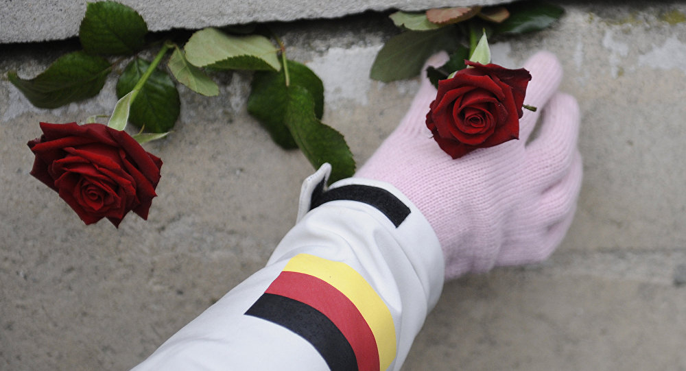 A woman places a rose in the former Berlin wall after a commemoration of the 20th anniversary of the fall of the Berlin Wall on 9 November 1989 at the wall memorial Bernauer Strasse in Berlin, Germany, on 9 November 2009