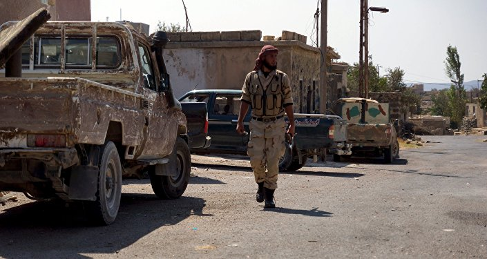 A Free Syrian Army fighter walks near military vehicles during what they said was preparations for an operation to strike at forces loyal to Syria's president Bashar Al-Assad in order to break a siege on the city of Beit Gin located in western countryside of Damascus in Deraa, Syria September 30, 2015