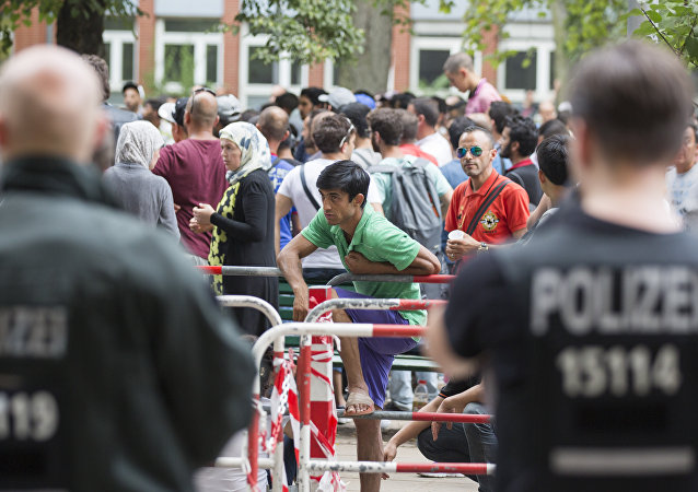 Police stand next to asylum seekers waiting in front of the reception center for refugees in Berlin, Germany, Friday, Aug. 7, 2015