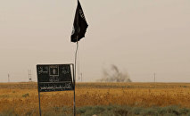 Smoke rises in the distance behind an Islamic State (IS) group flag and banner after Iraqi Kurdish Peshmerga fighters reportedly captured several villages from IS group jihadists in the district of Daquq, south of the northern Iraqi multi-ethnic city of Kirkuk on September 11, 2015