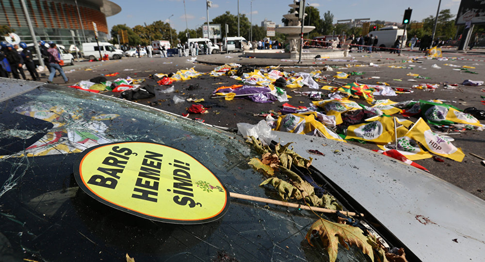 A placard that reads in Turkish: 'Peace Immediately Now' , is seen at the site of an explosion with the bodies of victims covered with flags and banners in the background, in Ankara, Turkey