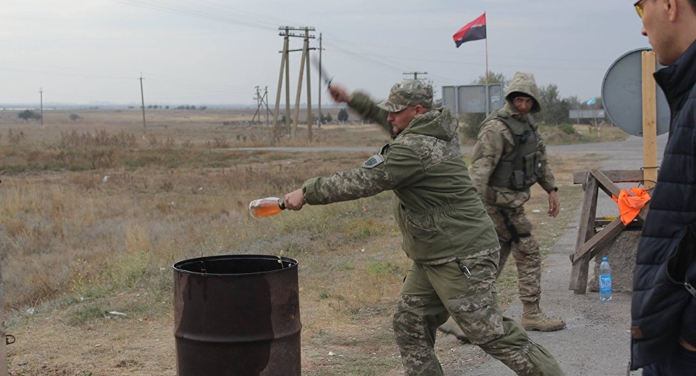 Right Sector activist smashes a bottle of expensive alcohol over a barrel.