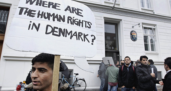 Some thirty Syrian refugees hold banners in Copenhagen, Denmark