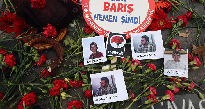 This photo taken on October 12, 2015 shows pieces of the traditional bread simits, a banner reading 'Peace Now' , and photos of victims at the site of the October 10 bombings in Ankara