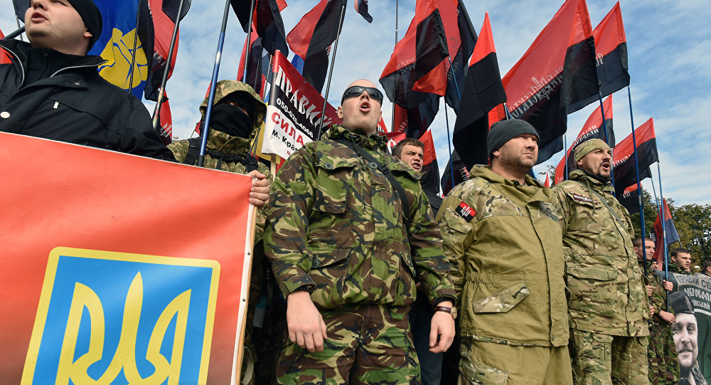 Members of far right movement Right Sector and supporters of nationalists parties wave flags as they attend a rally in Kiev on October 14, 2015