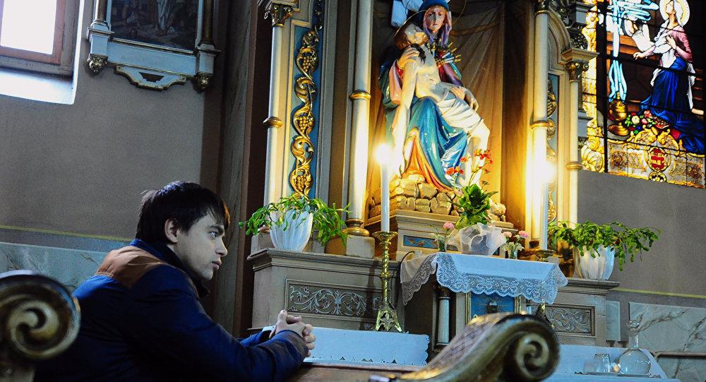 A man prays at the St George Roman Catholic Church in the city of Uzhgorod, in the Transcarpathian region, western Ukraine, on March 1, 2014
