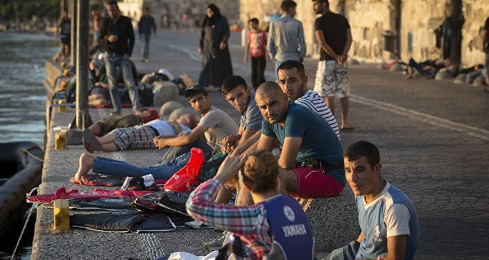 Migrants rest on an embankment of the port while waiting to be registered at the southeastern island of Kos, Greece, Wednesday, Aug. 19, 2015
