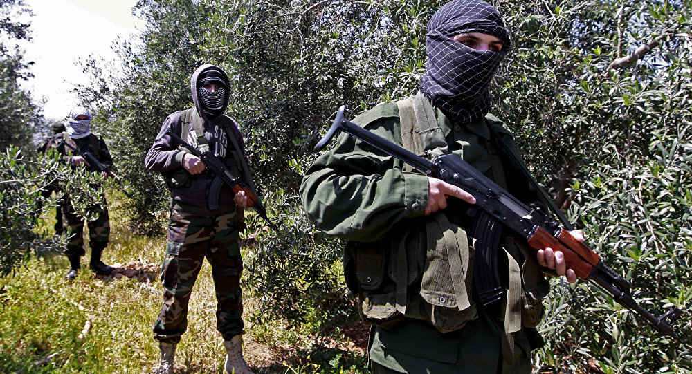 In this Friday, April 12, 2013 photo, members of the Lebanese pro-Syrian Popular Committees stand guard at the Lebanon-Syria border, near the northeastern Lebanese town of al-Qasr, Lebanon. Masked men in camouflage toting Kalashnikov rifles fan out through a dusty olive orchard.