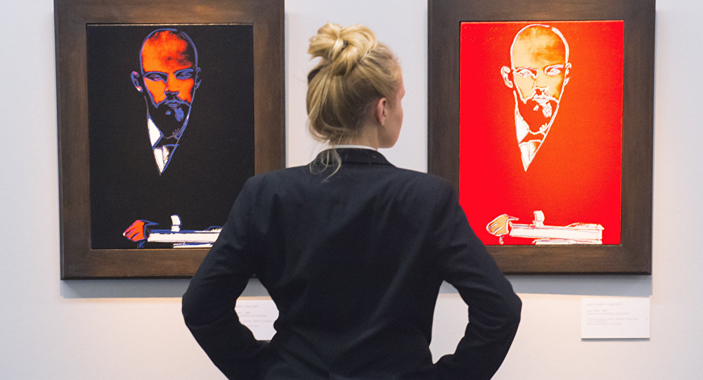 A woman stands in front of portraits of former Soviet Union leader Vladimir Lenin 'Lenin', Black, (1986), left, and 'Lenin', Red, (1986), right, by US artist Andy Warhol in the exhibition 'POP. David Hockney, Uwe Lausen, Andy Warhol' during the press preview in the museum Gunzenhauser in Chemnitz, eastern Germany, Friday, June 19, 2015