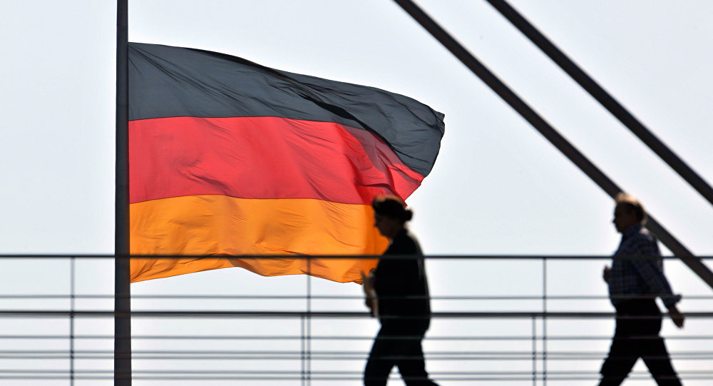 People pass a giant German National flag on the Reichstag, which houses the German parliament Bundestag, as they cross a bridge between two office buildings on Thursday, April 2, 2009 in Berlin