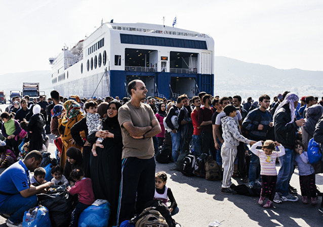 Refugees and migrants line up to board a ferry after arriving on the Greek island of Lesbos on October 16, 2015