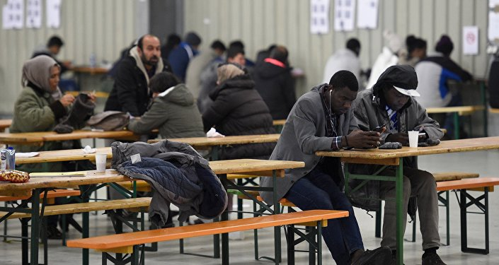 File Photo: Migrants use their cell phones in a canteen in a refugee camp in Celle, Lower-Saxony, Germany October 15, 2015.