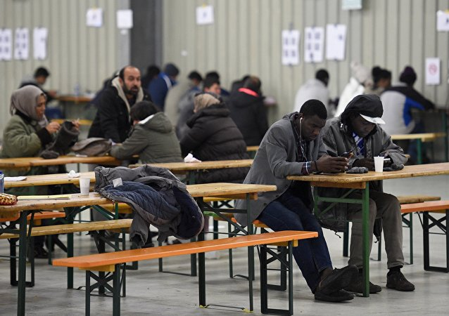 Migrants use their cell phones in a canteen in a refugee camp in Celle, Lower-Saxony, Germany October 15, 2015.